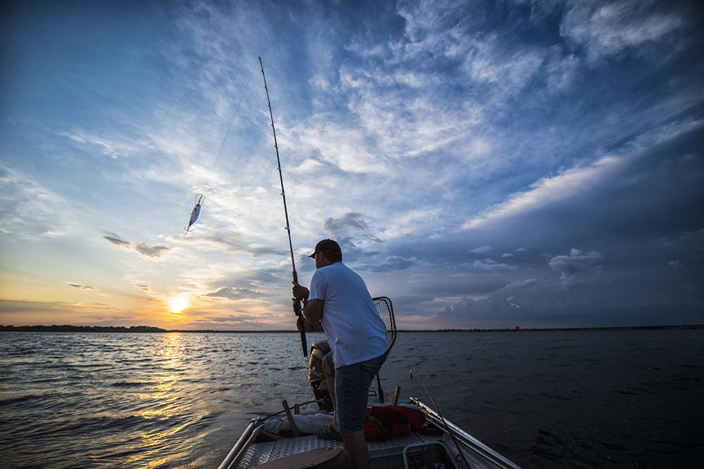 大海原に船を浮かべて釣りをする男性